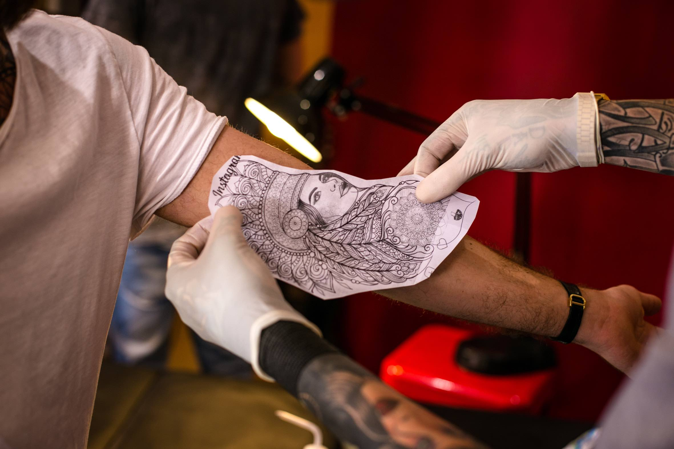 Duran Niemach placing a stencil on a client at SA Hardcore Tattoos