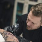Adam Megens tattooing a loyal client