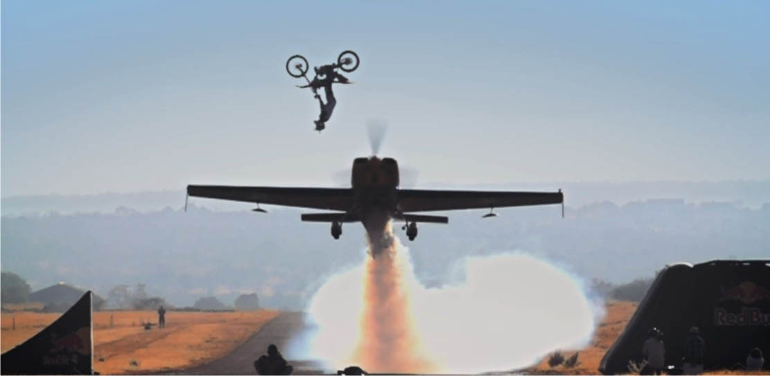 Freestyle Motocross rider Nick De Wit backflips over a low flying plane