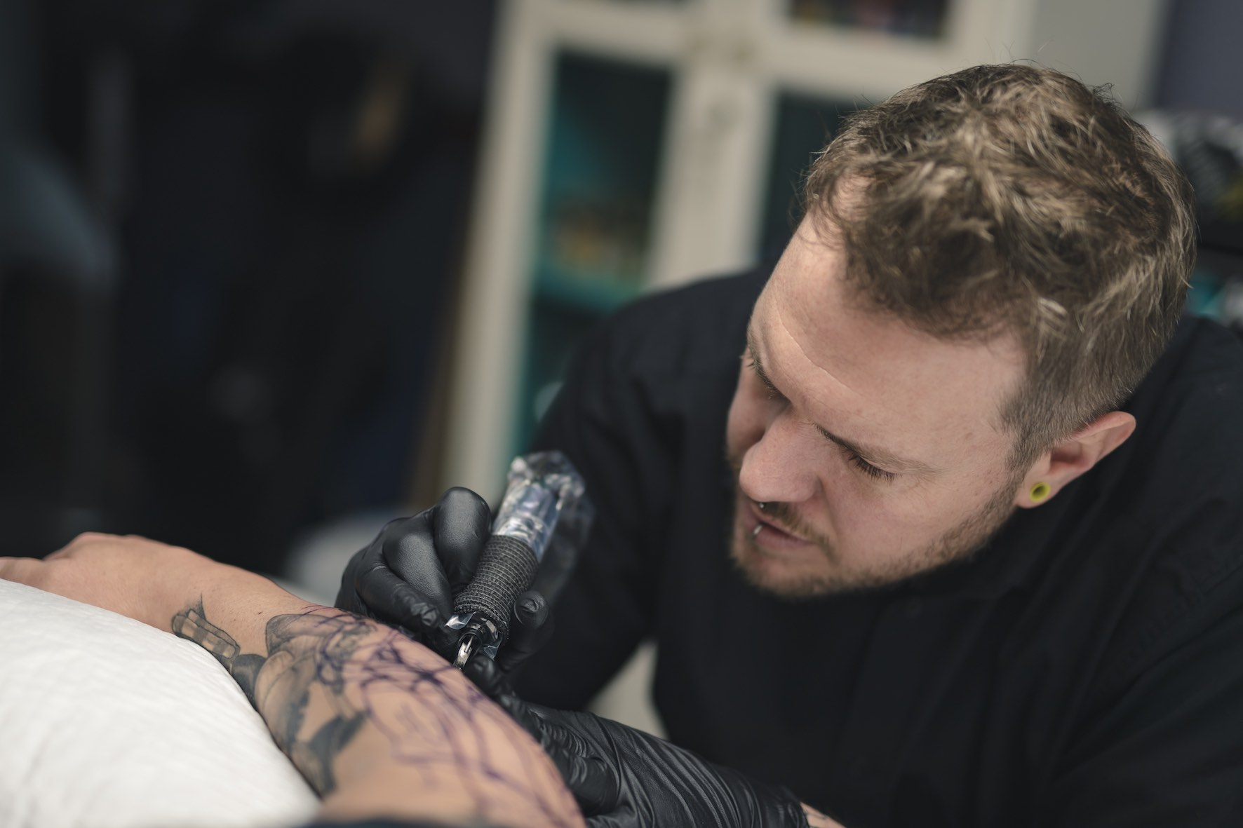 Adam Megens tattooing a loyal client