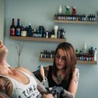 Lileen van den Berg tattooing at client at Artrageous Tattoos