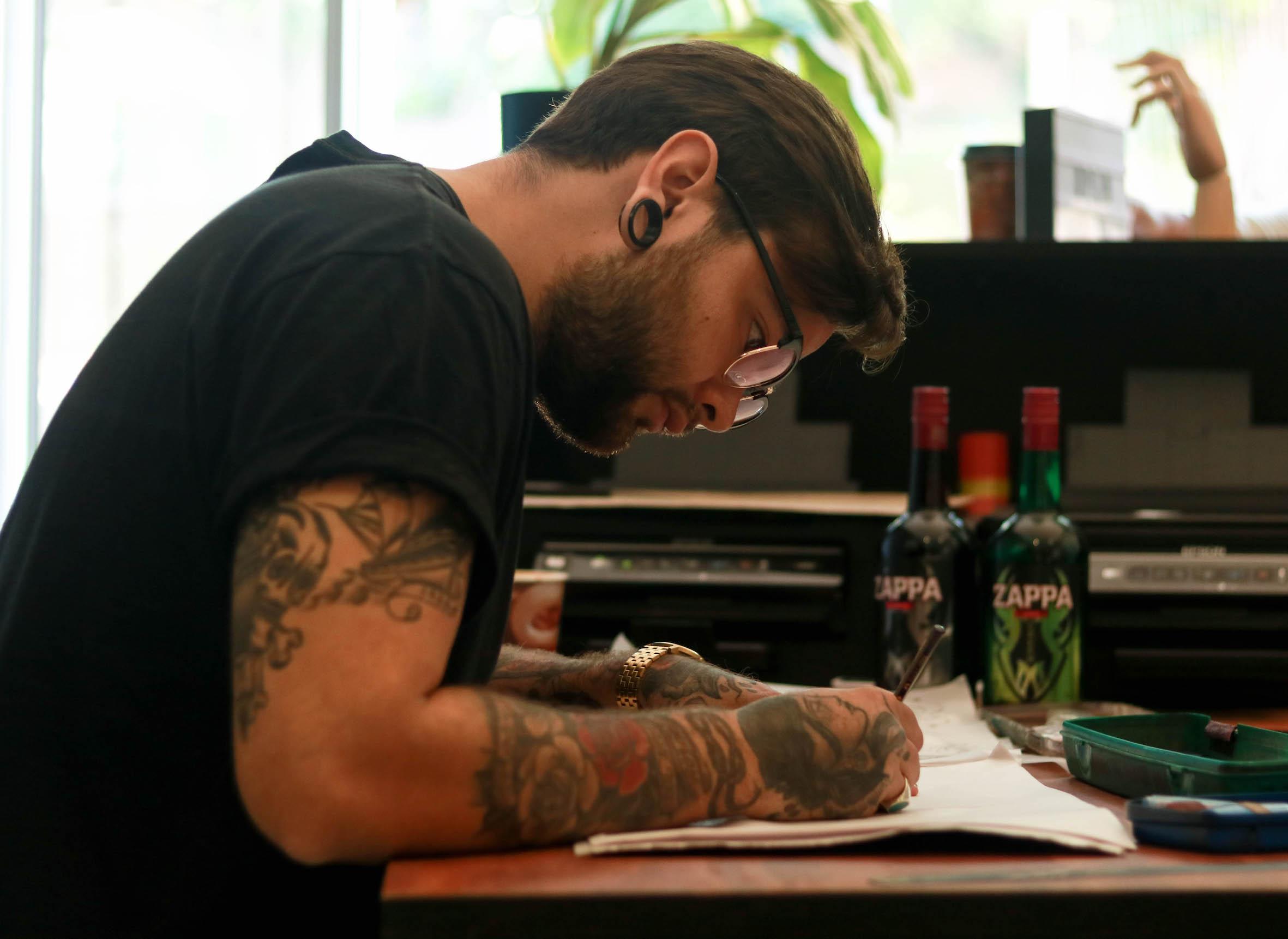 Tattoo Artist, Mason Murdey designs a tattoo for a client