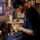 Nic Lewis preparing to tattoo a client