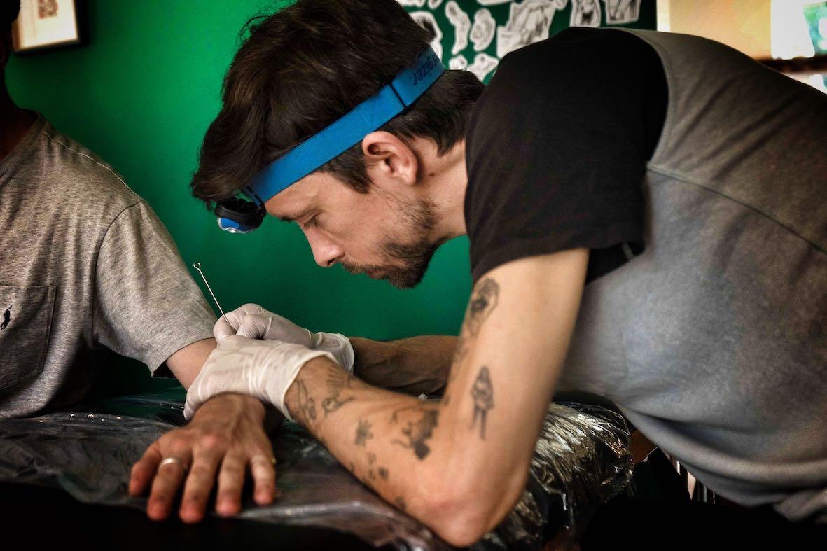 Max Eru handpoke tattooing a client