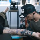 Bryan Du Rand freehand drawing the tattoo design on a client