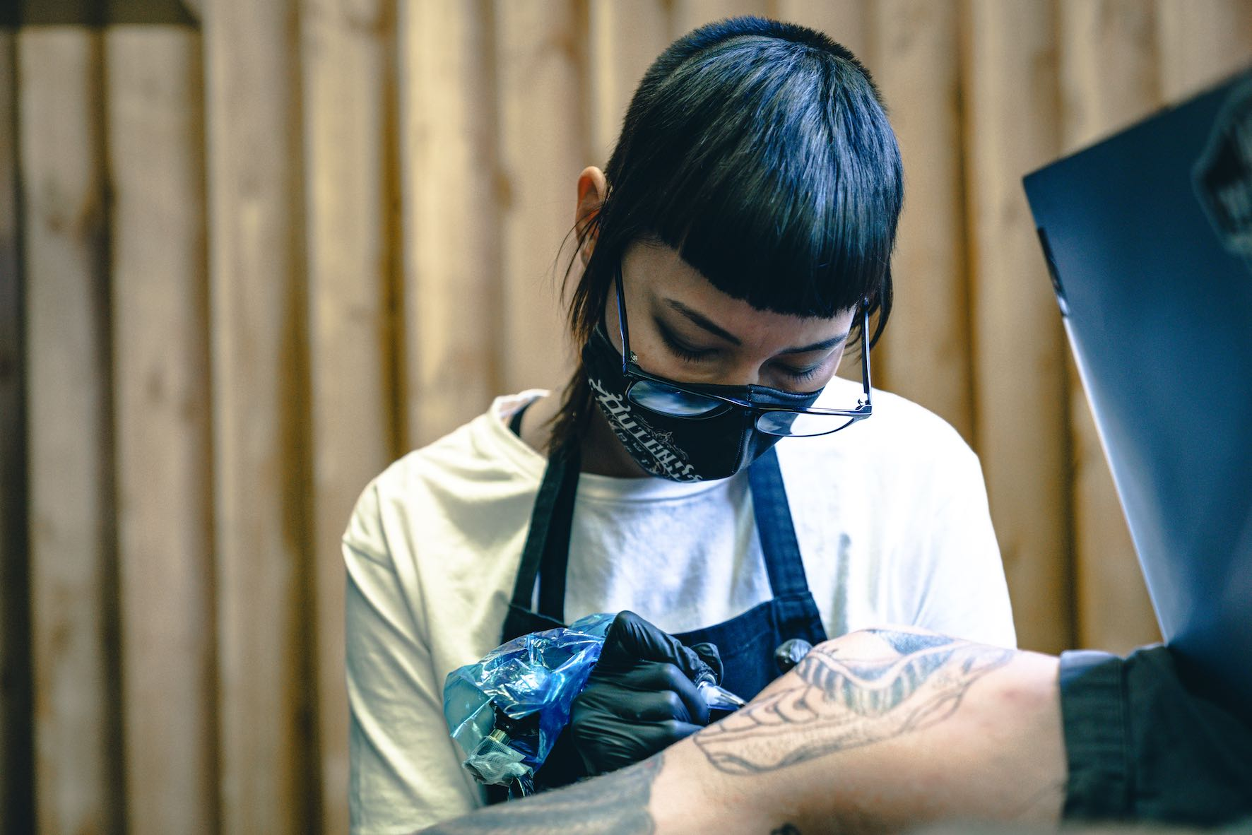 Romi Ding tattooing a client at Outcast Tattoos 818