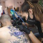 Alyssa van der Merwe tattooing a client at SheKnows Ink
