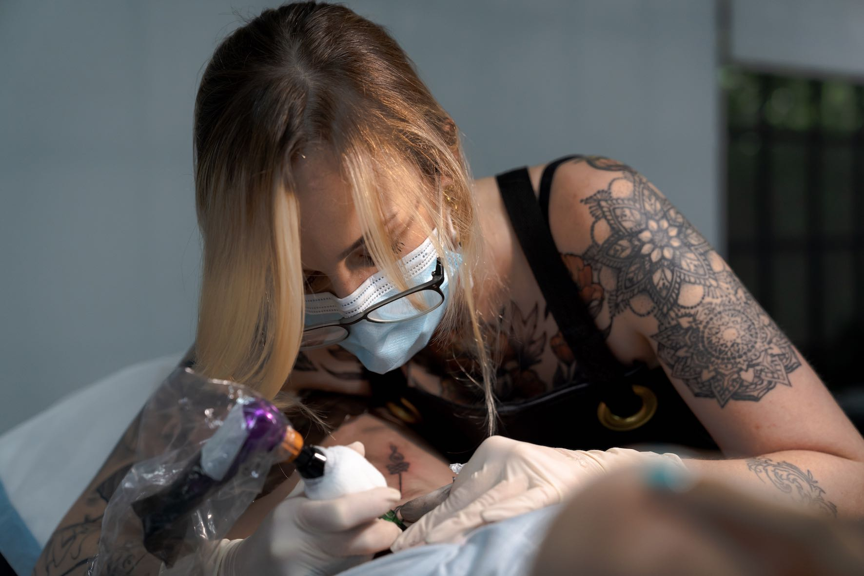 Jade Alexandra completing a tattoo on her client